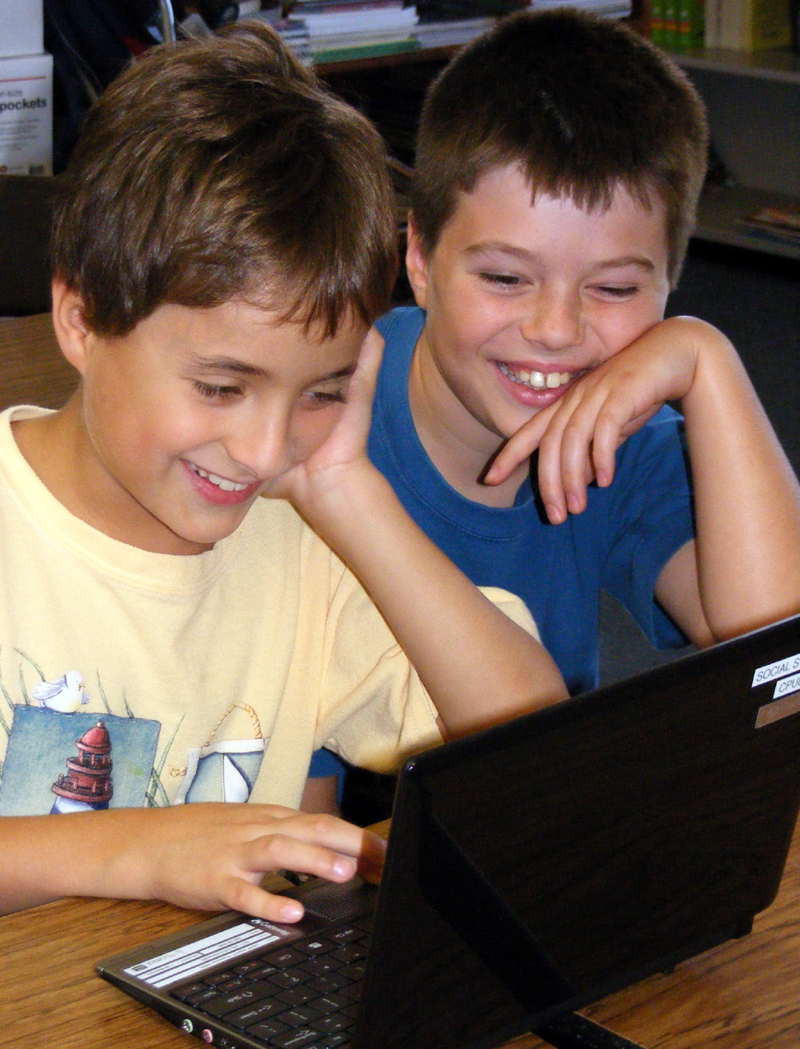 Two boys laughing over computer